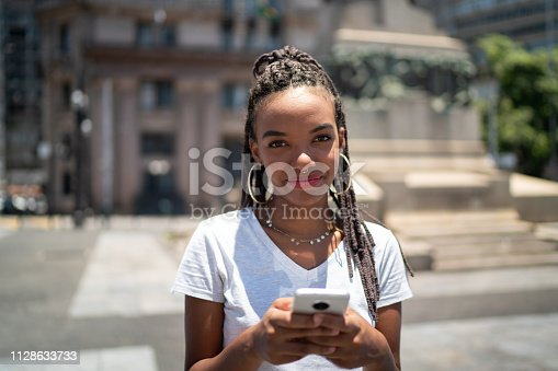 istock Afro latinx young woman in the city using smartphone portrait 1128633733