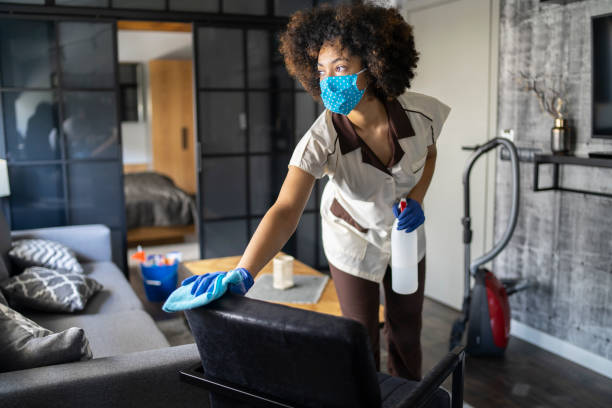 Afro maid with protective face mask while cleaning a hotel room in time of COVID-19 Pandemic stock photo