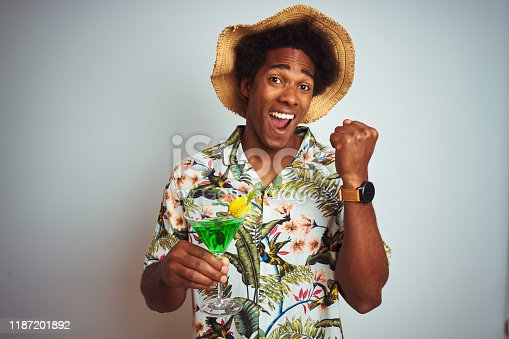 Afro man on holidays wearing summer hat drinking cocktail over isolated white background screaming proud and celebrating victory and success very excited, cheering emotion