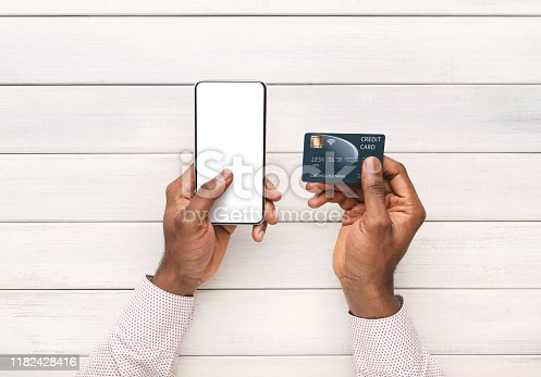 1173546354 istock photo Afro man using smartphone and credit card for online shopping 1182428416