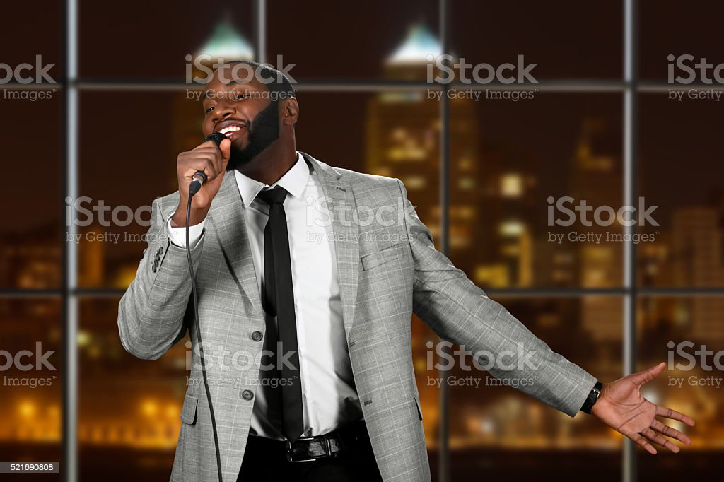 Afro man with microphone singing. stock photo