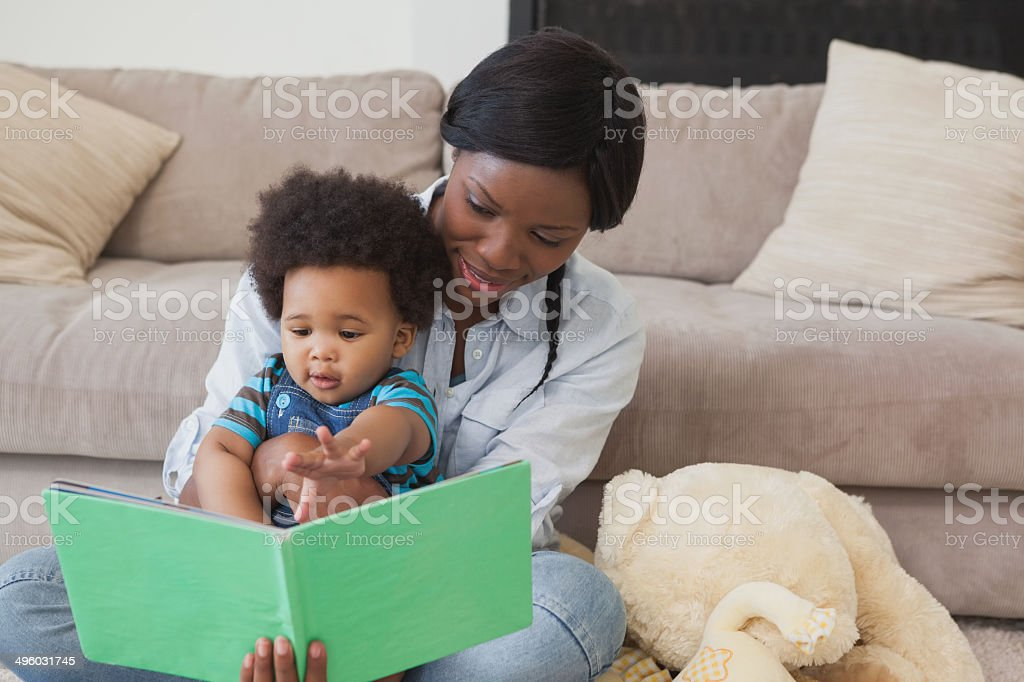 Afro mother with cute baby reading story book stock photo
