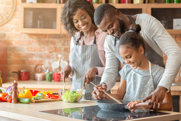 Afro parents teaching their daughter how to cook stock photo