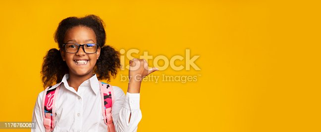 1176772377 istock photo Afro School Girl Pointing Thumbs At Copy Space, Yellow Background 1176760081