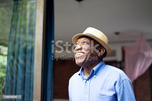 istock Afro Senior Looking Through The Window 1086889512