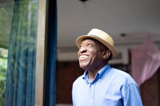 afro senior patrząc przez okno - nadzieja zdjęcia i obrazy z banku zdjęć