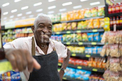 istock Afro senior man business owner / employee at supermarket 1128887915