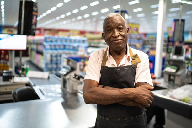 Afro senior man business owner / employee at supermarket Proud to say we're open for business sales clerk stock pictures, royalty-free photos & images