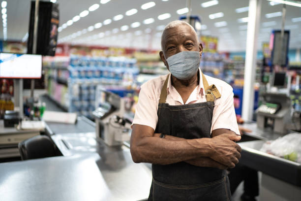 afro senior man business owner / employee with face mask at supermarket - servizi essenziali foto e immagini stock