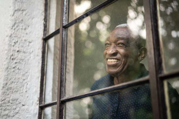 afro senior man looking through the window - uomo nostalgia foto e immagini stock