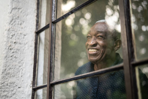 afro senior man looking through the window - old men window imagens e fotografias de stock