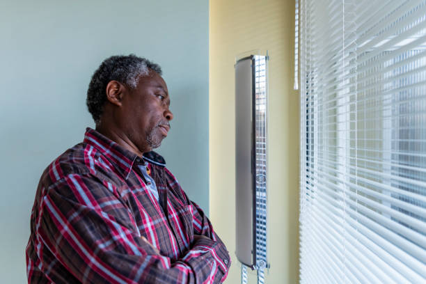 Homme aîné d'Afro regardant par la fenêtre - Photo