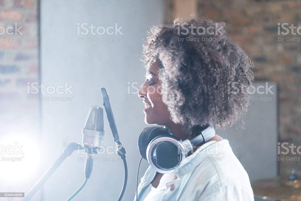Afro singer at a recording studio looking happy in front of the...