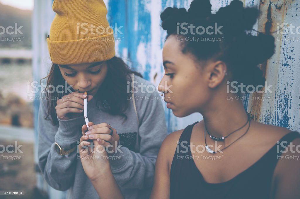 Afro teen lighting a cigarette for her grungy girl friend stock photo