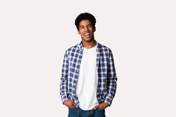 afro teenage guy posiert mit händen in taschen - mann freisteller stock-fotos und bilder