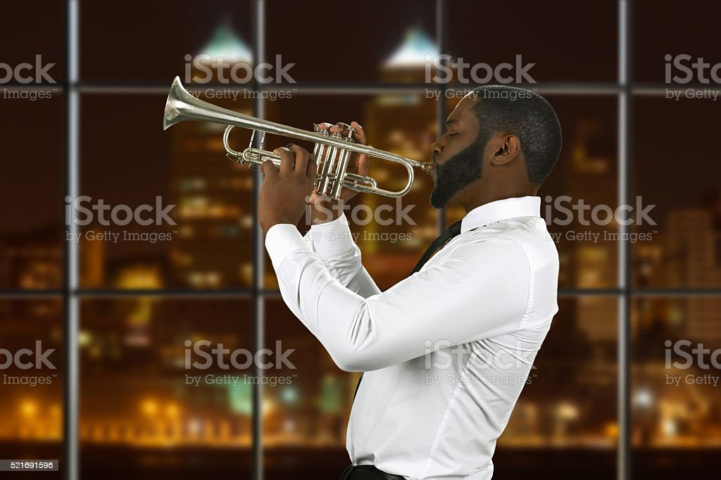 Afro trumpeter playing music. stock photo