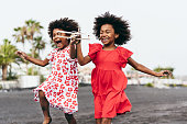 istock Afro twins sisters running on the beach while playing with wood toy airplane - Youth lifestyle and travel concept - Main focus on right kid face 1254994179