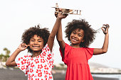 Afro twins sisters running on the beach while playing with wood toy airplane - Youth lifestyle and travel concept - Main focus on right kid face