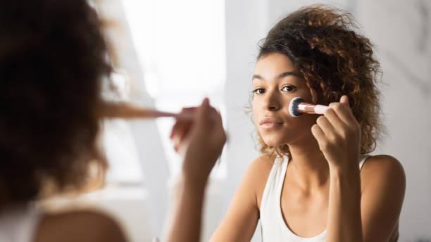 afro woman applying face powder with makeup brush in bathroom - woman make up imagens e fotografias de stock