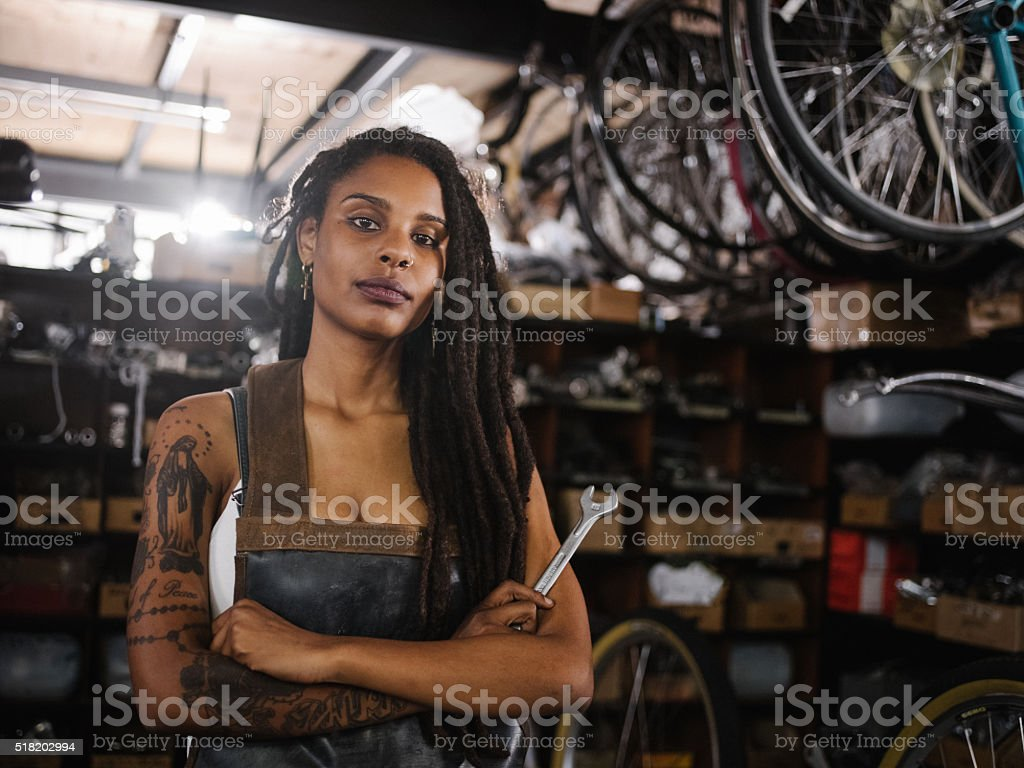 Afro woman bicycle mechanic looking proud in bike repair worksho stock photo