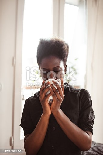 afro woman drink a tea at home