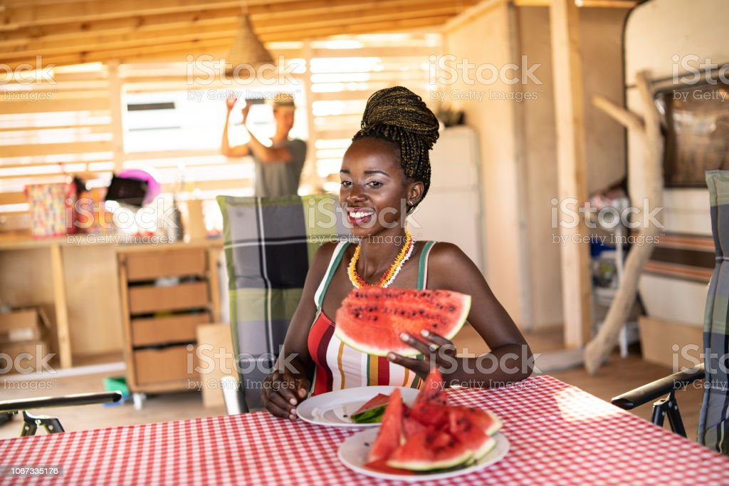 Afro woman eating watermelon stock photo