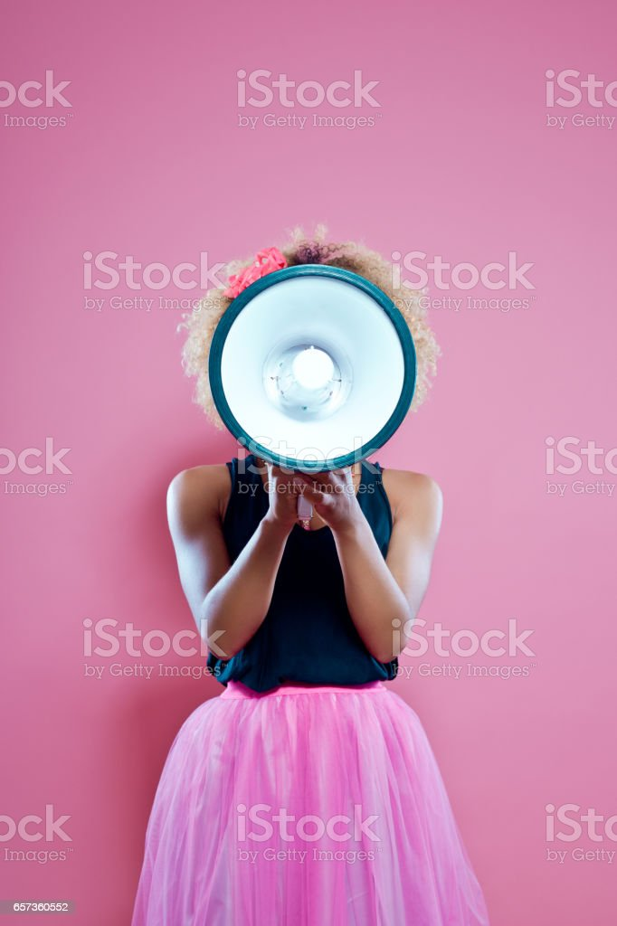 Afro woman holding screaming into megaphone stock photo