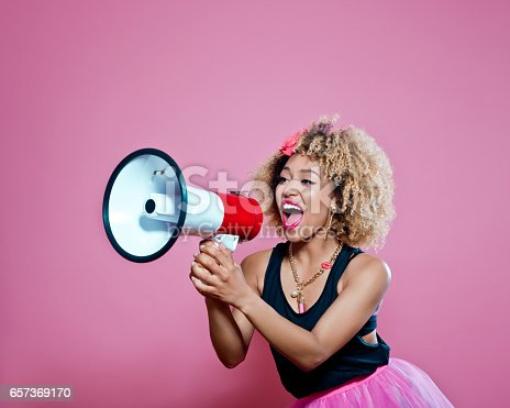 657442382istockphoto Afro woman holding screaming into megaphone 657369170