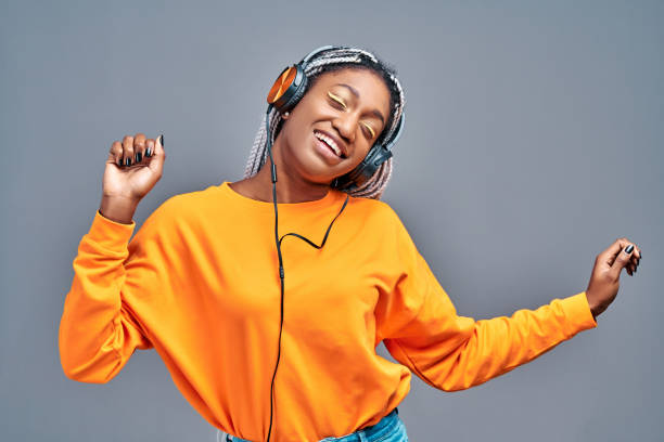 Afro woman in headphones listening to music and dancing over grey studio background stock photo