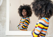 Afro Woman looking at her reflection in the mirror