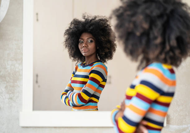 Afro Woman looking at her reflection in the mirror Afro Woman looking at her reflection in the mirror mirror stock pictures, royalty-free photos & images