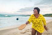 istock Afro woman playing beach tennis 1180105244
