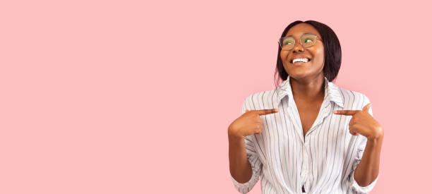 afro kobieta wskazując palce na siebie na różowym tle, panorama - indywidualność zdjęcia i obrazy z banku zdjęć