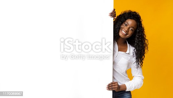 1168002879 istock photo Afro woman staying next to blank board 1170089567