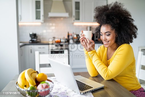 822557072 istock photo Afro Woman using laptop at home and drinking coffee 1137915870