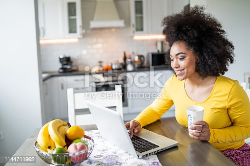 822557072 istock photo Afro Woman using laptop at home and drinking coffee 1144711962