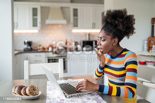 822557072 istock photo Afro Woman using laptop at home 1155040064