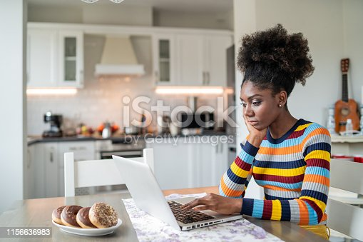 822557072 istock photo Afro Woman using laptop at home 1156636983