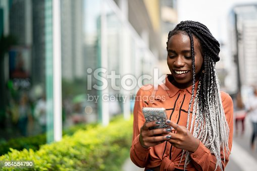 istock Afro Woman Using Mobile at Street 964584790