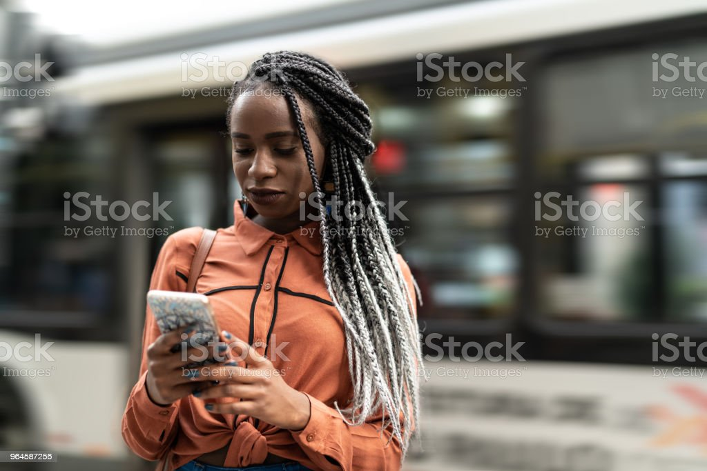 Afro Woman Using Mobile at Street stock photo