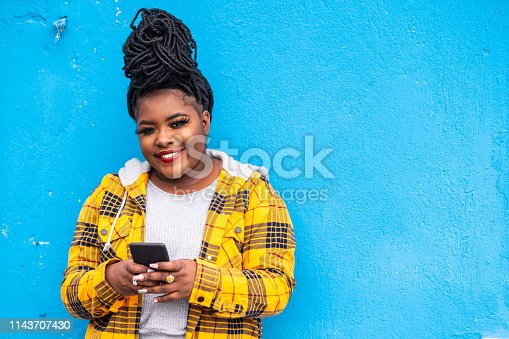 istock Afro woman using smart phone on a blue background 1143707430