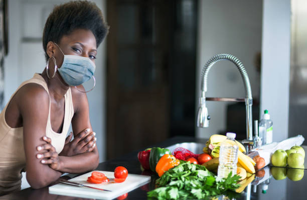 afro woman with mask at home in the kitchen stock photo