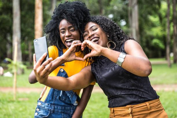 afro kvinnor nedstigningen tar selfie foton i parken - video call bildbanksfoton och bilder