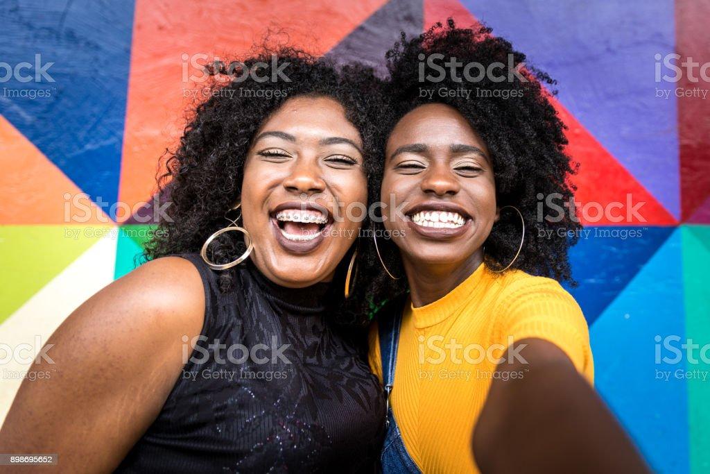 Descida de mulheres africanas tirando fotos de selfie no parque - foto de acervo
