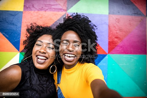 istock Afro women descent taking selfie photos in the park 898695654