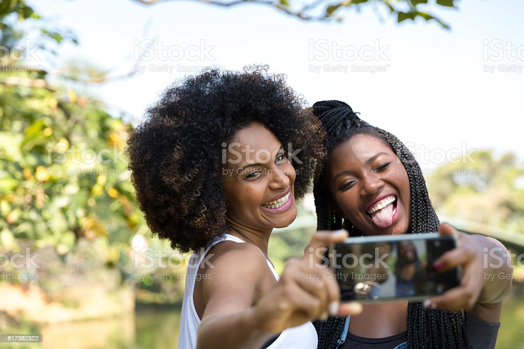 Afro women taking selfie photos in the park stock photo