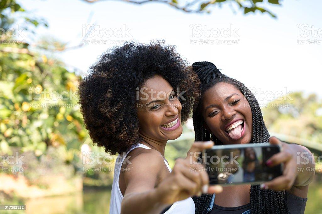 Afro women taking selfie photos in the park - foto de acervo