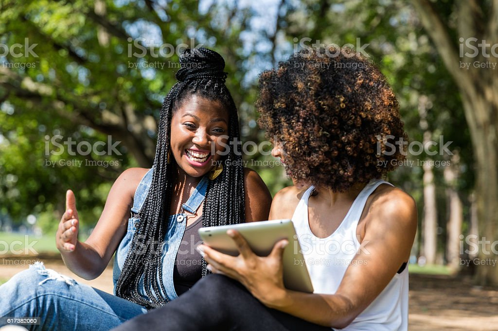 Afro women using tablet computer in the park - foto de acervo