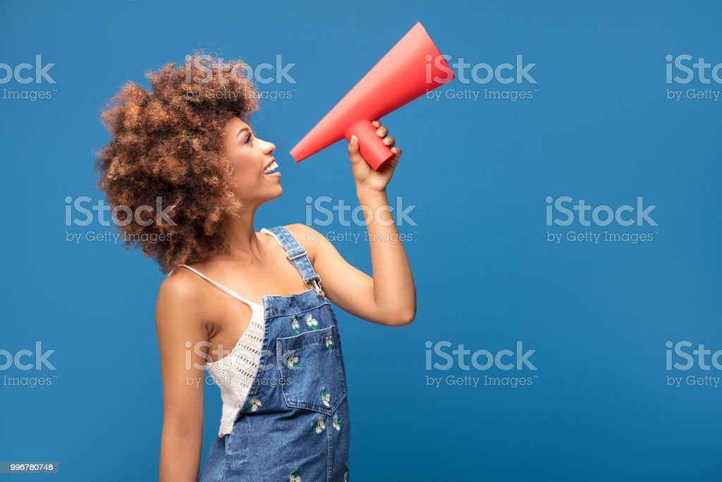 Afro young girl screaming by red megaphone. stock photo