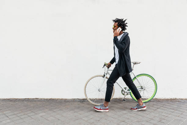 Afro young man using mobile phone and fixed gear bicycle. stock photo